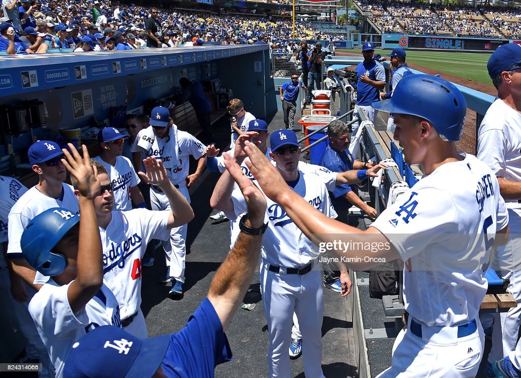 Corey Seager #5 of the Los Angeles Dodgers is greeted in the dugout after scoring a run on a single by Cody Bellinger #35 of the Los Angeles Dodgers in the first inning of the game against the San Francisco Giants at Dodger Stadium on July 29, 2017 in Los Angeles, California.