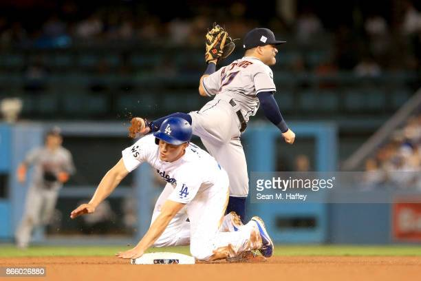 Corey Seager of the Los Angeles Dodgers is tagged out at second base by Jose Altuve of the Houston Astros on a double play during the fifth inning in...