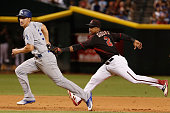 Corey Seager of the Los Angeles Dodgers is tagged out in a run down by infielder Jean Segura of the Arizona Diamondbacks during the MLB game at Chase...
