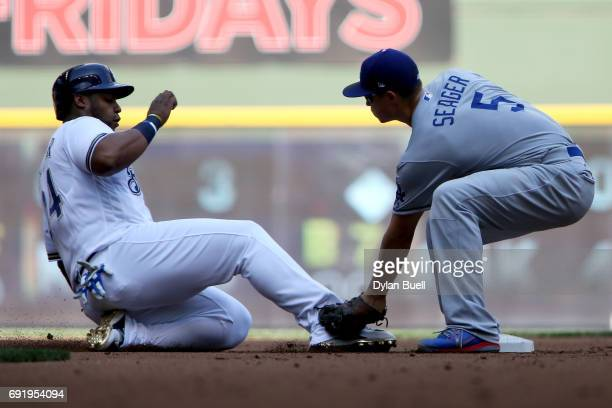 Corey Seager of the Los Angeles Dodgers tags out Jesus Aguilar of the Milwaukee Brewers at second base during a pickoff in the first inning at Miller...