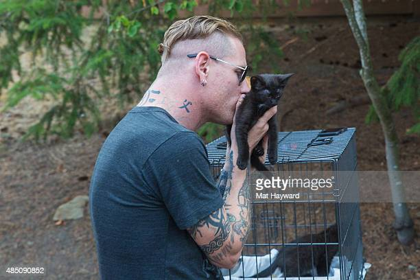 Corey Taylor of Slipknot holds a kitten brought by Motley Zoo Animal Rescue during Pain In The Grass hosted by 999 KISW at White River Amphitheater...