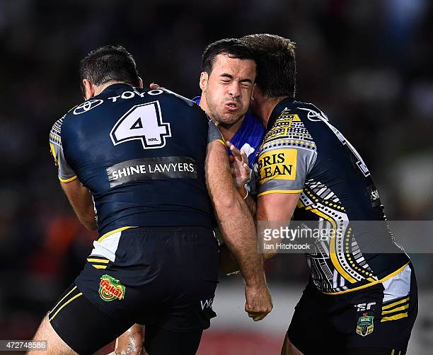 Corey Thompson of the Bulldogs is tackled by Kane Linnett and Gavin Cooper of the Cowboys during the round nine NRL match between the North...