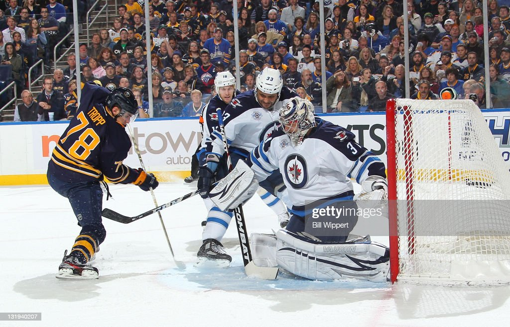<a gi-track='captionPersonalityLinkClicked' href=/galleries/search?phrase=Corey+Tropp&family=editorial&specificpeople=5483748 ng-click='$event.stopPropagation()'>Corey Tropp</a> #78 of the Buffalo Sabres scores his first NHL goal against <a gi-track='captionPersonalityLinkClicked' href=/galleries/search?phrase=Dustin+Byfuglien&family=editorial&specificpeople=672505 ng-click='$event.stopPropagation()'>Dustin Byfuglien</a> #33 and Ondrej Pavelec #31 of the Winnipeg Jets at First Niagara Center on November 8, 2011 in Buffalo, New York.