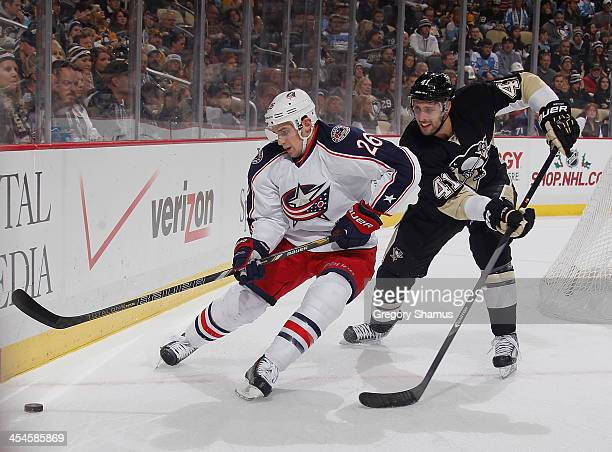 Corey Tropp of the Columbus Blue Jackets skates for the loose puck alongside Robert Bortuzzo of the Pittsburgh Penguins on December 9 2013 at Consol...