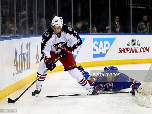 Corey Tropp of the Columbus Blue Jackets takes the puck as Dylan McIlrath of the New York Rangers falls at Madison Square Garden on December 12 2013...