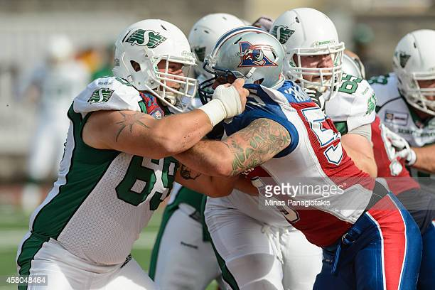 Corey Watman of the Saskatchewan Roughriders blocks Gabriel Knapton of the Montreal Alouettes during the CFL game at Percival Molson Stadium on...