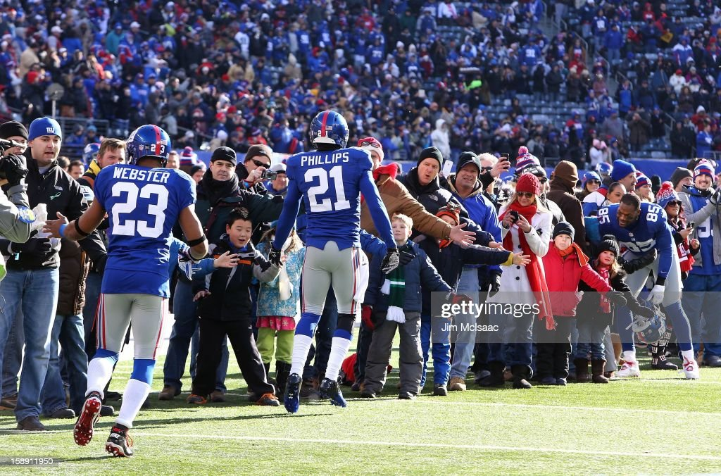 Corey Webster #23, Kenny Phillips #21 and Martellus Bennett #85 of the New York Giants greets students, parents and faculty of Sandy Hook Elementary School as well as residents of Newtown, Connecticut as they attend the NFL game between the New York Giants and the Philadelphia Eagles at MetLife Stadium on December 30, 2012 in East Rutherford, New Jersey. The Giants defeated the Eagles 42-7.