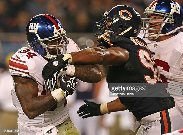 Corey Wootton of the Chicago Bears gets his arm on Brandon Jacobs of the New York Giants at Soldier Field on October 10 2013 in Chicago Illinois The...
