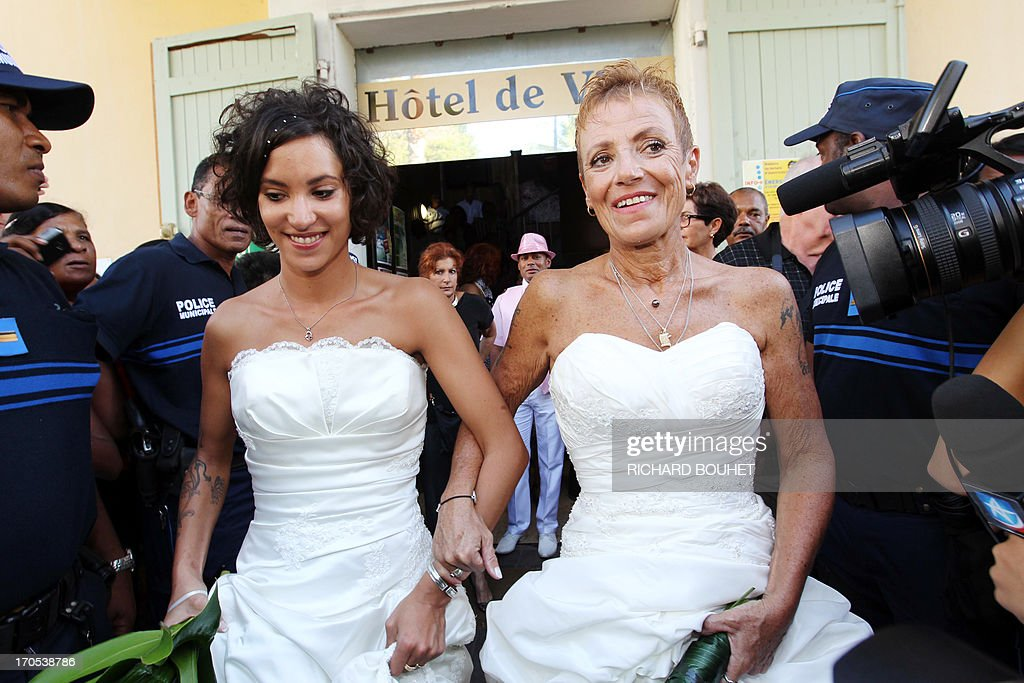 Corinne Denis (R) and Laurence Cerveaux (L) celebrate after being declared married at Saint-Paul de la Reunion city hall during the first official gay marriage French island of La Reunion. France is the 14th country to legalise same-sex marriage, an issue that has also divided opinion in many other nations. The definitive vote in the French parliament came on April 23 when the law was passed legalising both homosexual marriages and adoptions by gay couples.