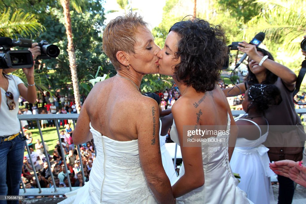 Corinne Denis (L) and Laurence Cerveaux (R) kiss each other after being declared married at Saint-Paul de la Reunion city hall during the first official gay marriage French island of La Reunion. France is the 14th country to legalise same-sex marriage, an issue that has also divided opinion in many other nations. The definitive vote in the French parliament came on April 23 when the law was passed legalising both homosexual marriages and adoptions by gay couples.