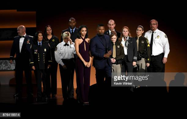 Corinne Foxx and Jamie Foxx and first responders pose onstage during the 2017 American Music Awards at Microsoft Theater on November 19 2017 in Los...