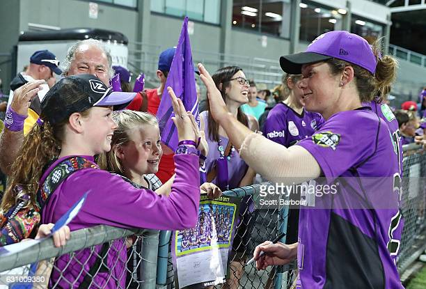 Corinne Hall of the Hurricanes signs autographs for supporters in the crowd during the Women's Big Bash League match between the Sydney Thunder and...