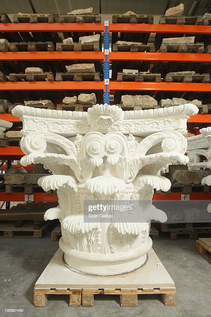 A Corinthian capital cast in plaster stands among other architectural elements stacked at the Schlossbauhuette studio where a team of sculptors is creating decorative elements for the facade of the Berliner Schloss city palace on November 11, 2011 in Berlin, Germany. The Berliner Schloss was the residence of the Prussian Kaiser and was among the major architectural landmarks of Berlin until it was heavily damaged by Allied bombing in 1945. The communist authorities of East Berlin demolished the building in the 1950s, and today's Berlin government is pursuing an ambitious project to rebuild the palace according to a design by Italian architect Franco Stella, which will recreate the facade of the building but with a modern interior at a cost of approximately EUR 590 million. The Humboldt Forum, the foundation leading the project, has given the Schlossbauhuette sculptors the formidable task of recreating the hundreds of architectural elements that decorated the facade, and though some original pieces were saved, more often the sculptors have only old black and white photos as reference.