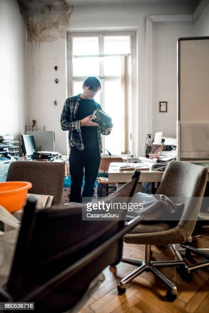 Corious Office Worker In His Messy Office Holding An Old Device