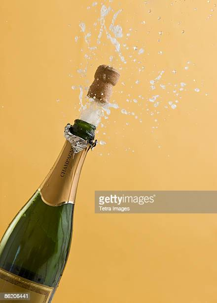 Cork exploding from champagne bottle