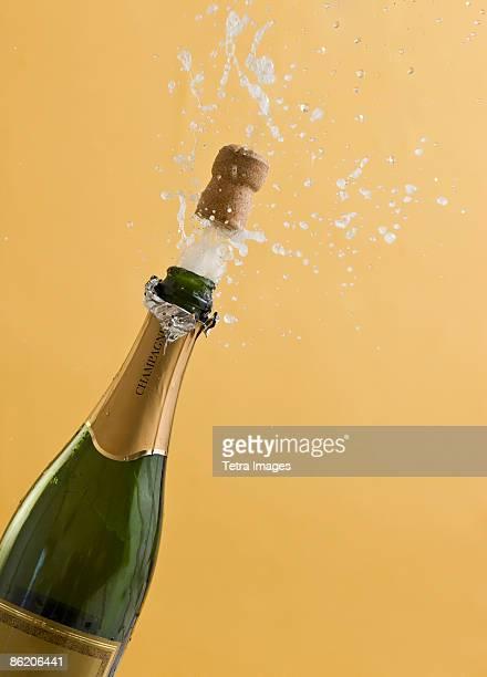 Cork exploding from champagne bottle