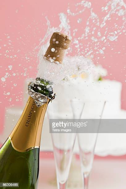 Cork exploding from champagne bottle with wedding cake in background