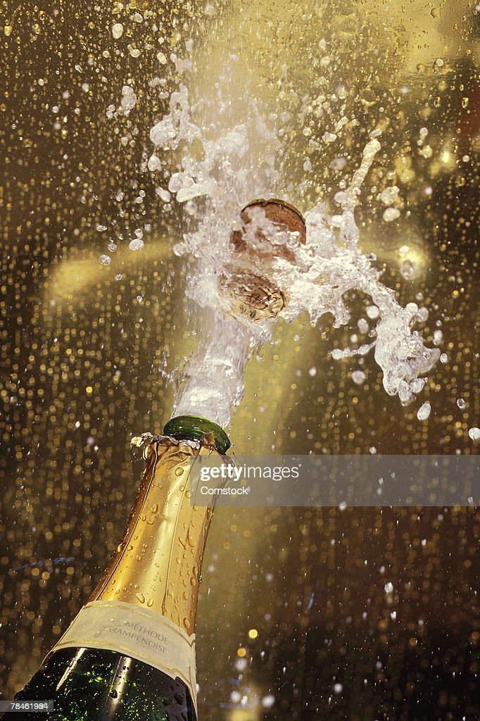 Cork popping on champagne bottle