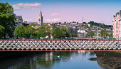 Cork, Ireland - May 21, 2014: St. Vincent's Foot Bridge on Pope's Quay, Cork City, Ireland with the famous Shandon Bells in the distance on a bright Summer's evening.
