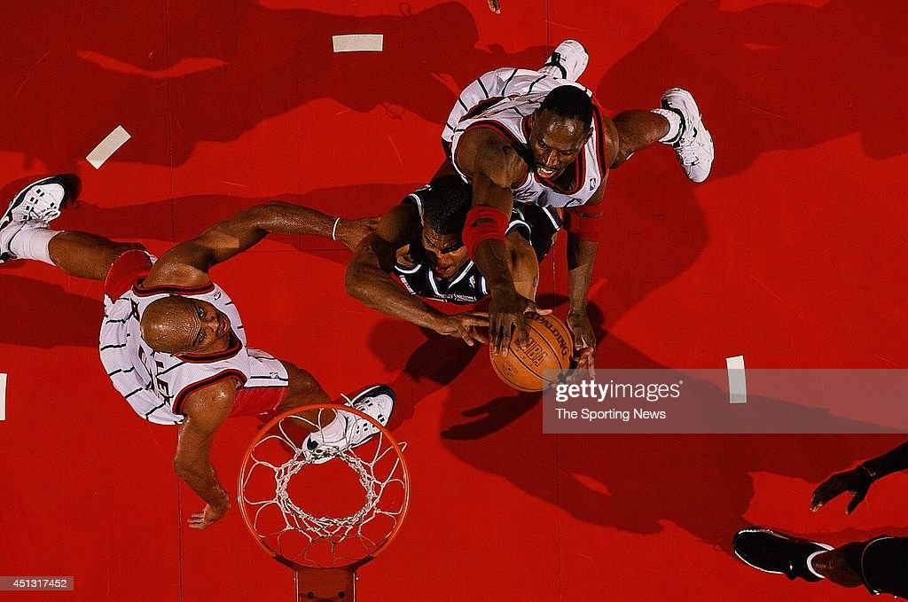 Corliss Williamson of the Sacramento Kings goes to the basket against Charles Barkley and Kevin Willis of the Houston Rockets during the game on...