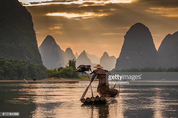 Cormorant and fisherman at dawn on the Li River, Guilin, Yangshou, Guangxi Province, China, Asia