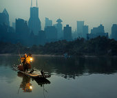 Cormorant fisherman in Shanghai against city background