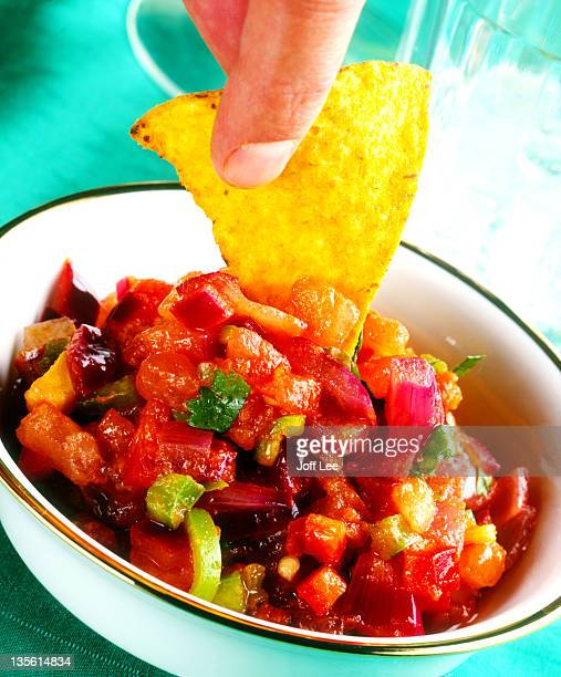 Corn chip being dipped in salsa