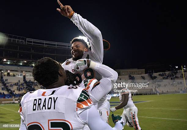 Corn Elder of the Miami Hurricanes celebrates with teammates after scoring the gamewinning touchdown against the Duke Blue Devils during their game...