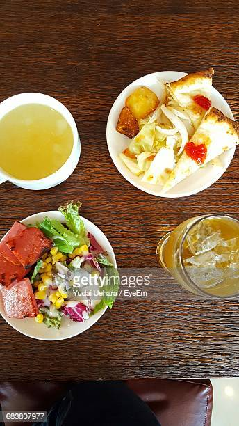 Corn Lettuce Salad And Cup Soup With Slice Of Pizza And Drink