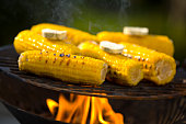 Corn on the cob with herb butter on barbecue grill, close up
