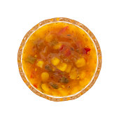 Top view of a portion of corn relish in a small glass bowl isolated on a white background.