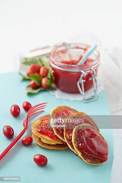 Cornel cherry jam with pancakes on chopping board