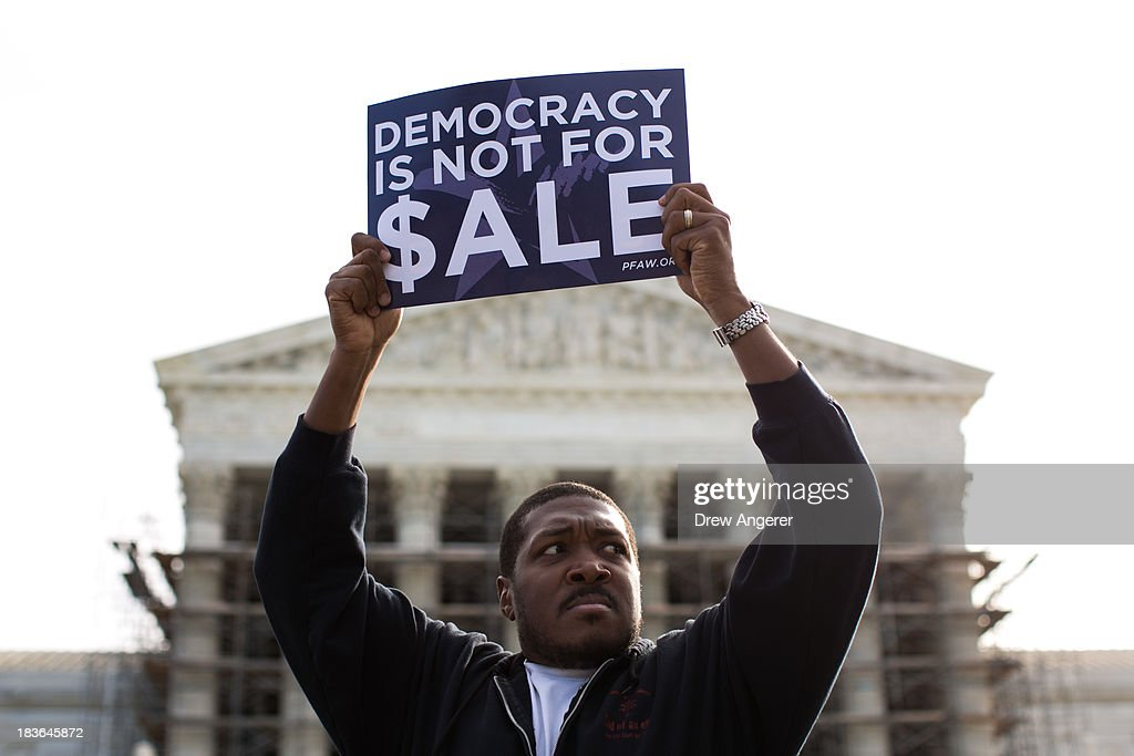 Cornell Woolridge holds a sign as he rallies against money in politics, at the Supreme Court in Washington, on October 8, 2013 in Washington, DC. On Tuesday, the Supreme Court heard oral arguments in McCutcheon v. Federal Election Committee, a first amendment case that will determine how much money an individual can contribute directly to political campaigns.