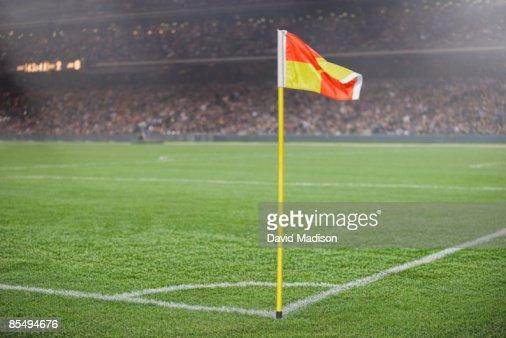 Corner flag on soccer field with spectators.