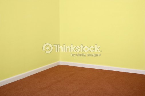 Corner of a room with brown carpet and yellow walls stock for Brown and yellow walls