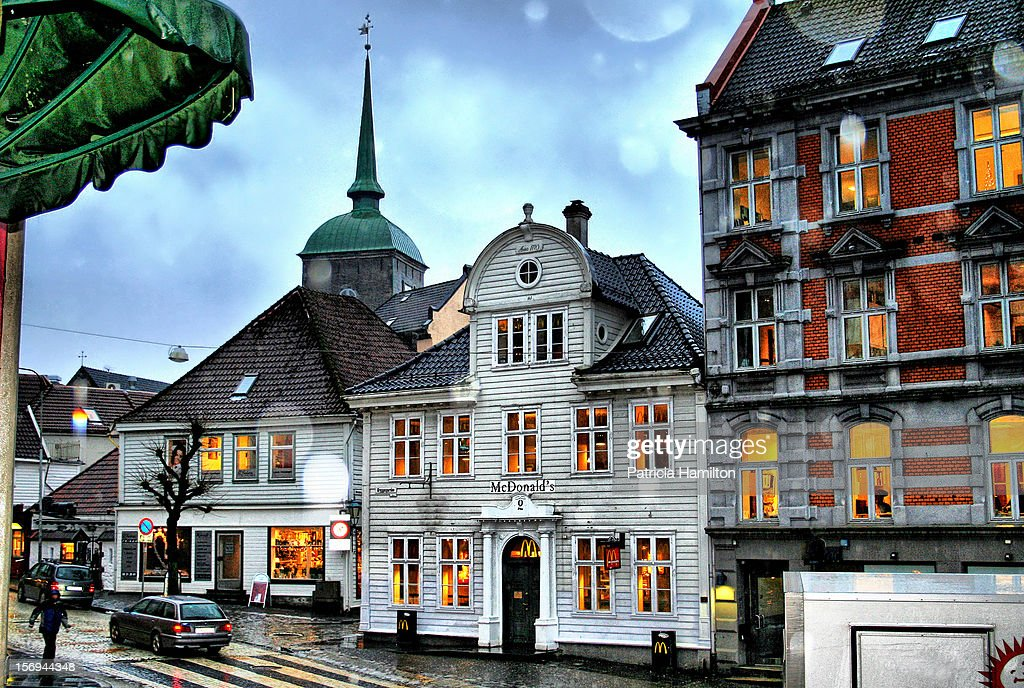 A corner of the streets of Bergen with large rain drops falling in front of the lens. Offices and shops.