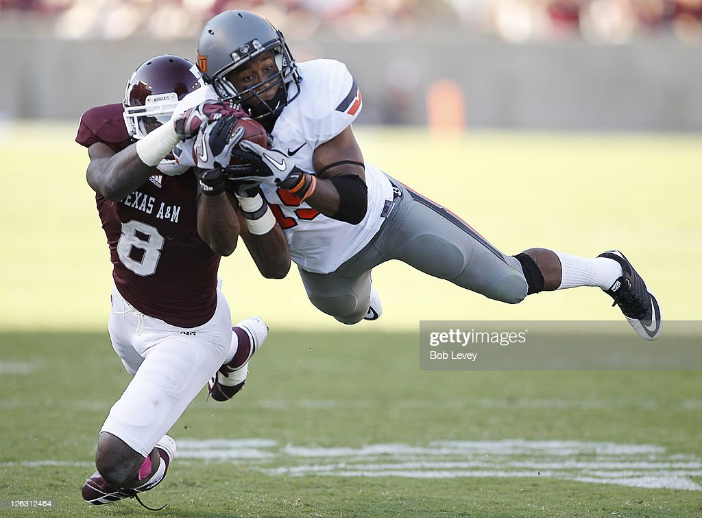 Cornerback Brodrick Brown #19 of the Oklahoma State Cowboys dives in front of wide receiver Jeff Fuller #8 of the Texas A&M Aggies for an interception at Kyle Field on September 24, 2011 in College Station, Texas. Oklahoma State won 30-29.