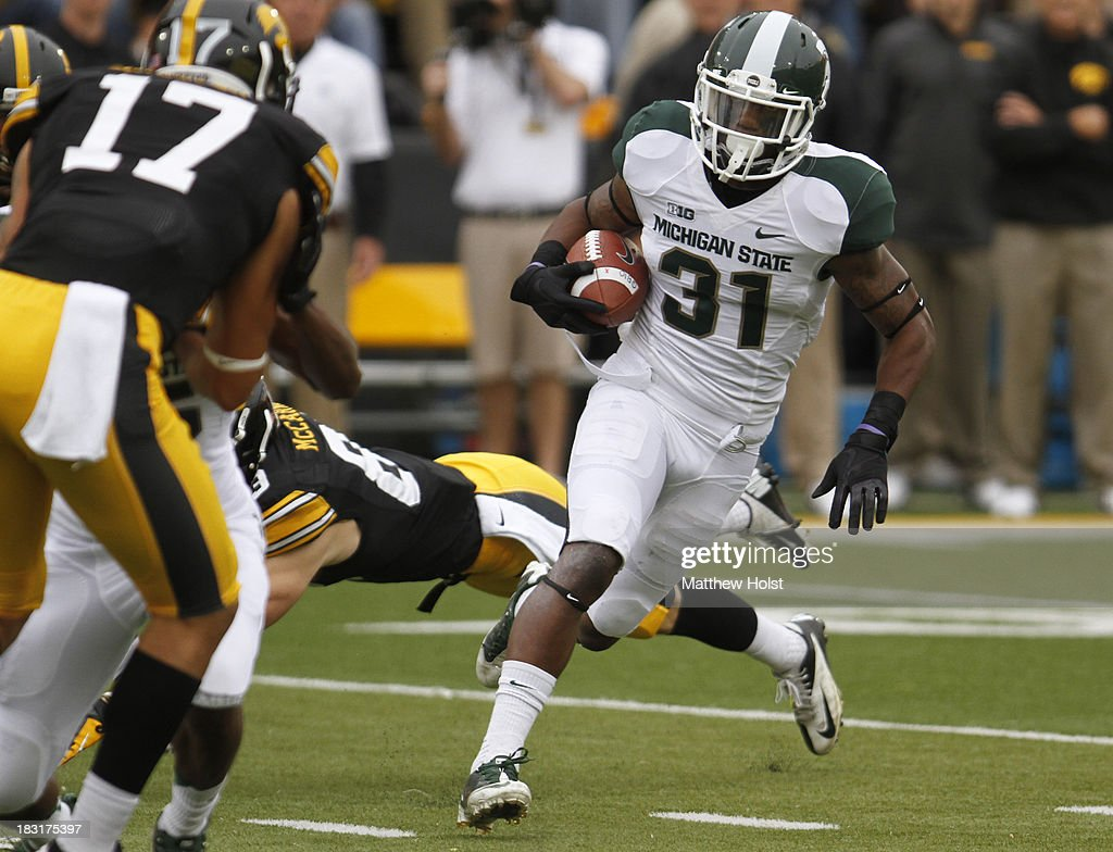 Cornerback Darqueze Dennard #31 of the Michigan State Spartans runs back an interception up field during the first quarter in front of wide receiver Riley McCarron #83 of the Iowa Hawkeyes on October 5, 2013 at Kinnick Stadium in Iowa City, Iowa. Michigan State won 26-14.
