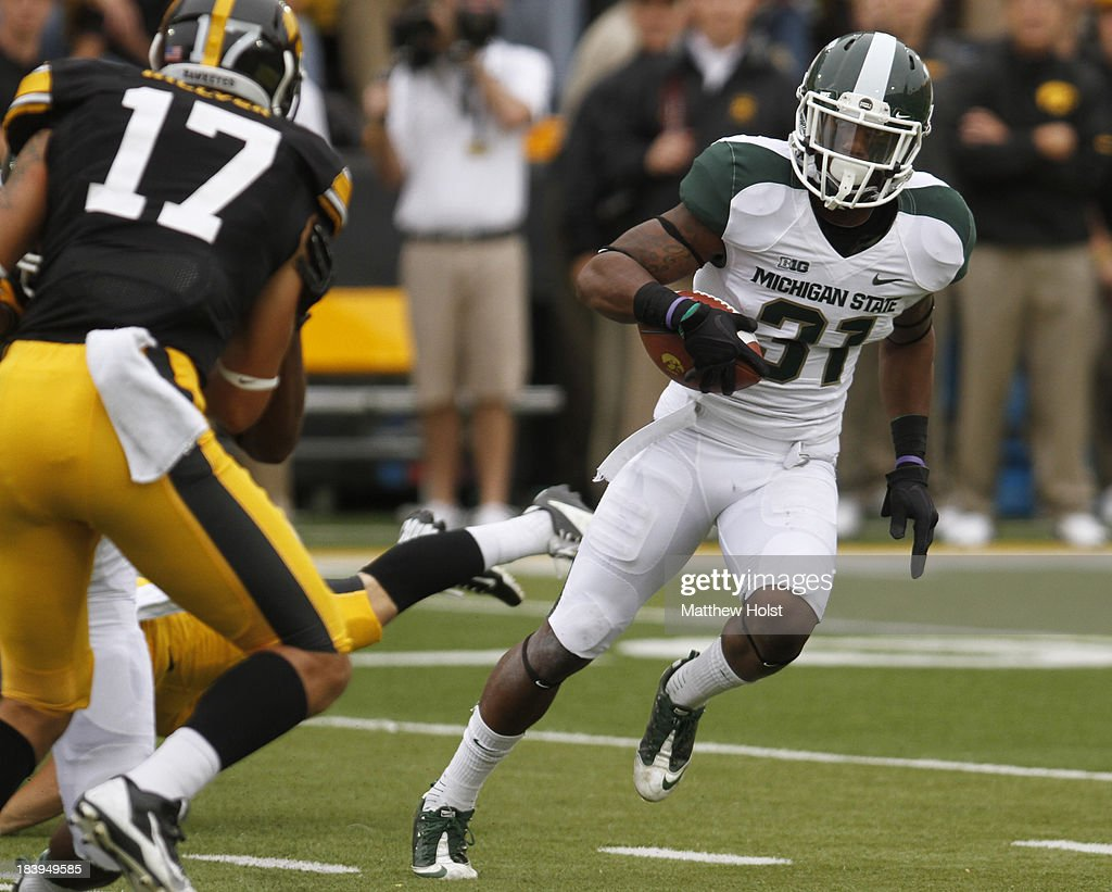 Cornerback Darqueze Dennard #31 of the Michigan State Spartans runs back an interception during the first quarter in front of wide receiver Jacob Hillyer #17 of the Iowa Hawkeyes on October 5, 2013 at Kinnick Stadium in Iowa City, Iowa. Michigan State won 26-14.