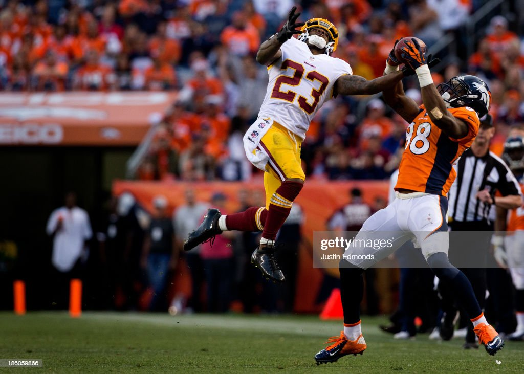 Cornerback <a gi-track='captionPersonalityLinkClicked' href=/galleries/search?phrase=DeAngelo+Hall&family=editorial&specificpeople=209065 ng-click='$event.stopPropagation()'>DeAngelo Hall</a> #23 of the Washington Redskins uses one hand to intercept the ball away from wide receiver <a gi-track='captionPersonalityLinkClicked' href=/galleries/search?phrase=Demaryius+Thomas&family=editorial&specificpeople=4536795 ng-click='$event.stopPropagation()'>Demaryius Thomas</a> #88 of the Denver Broncos during the fourth quarter at Sports Authority Field Field at Mile High on October 27, 2013 in Denver, Colorado. The Broncos defeated the Redskins 45-21.