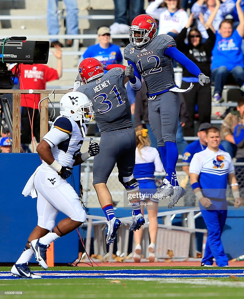 Cornerback Dexter McDonald #12 congratulates linebacker Ben Heeney #31 of the Kansas Jayhawks after Heeney intercepted a pass and ran it back to the one-yard-line during the game against the West Virginia Mountaineers at Memorial Stadium on November 16, 2013 in Lawrence, Kansas.