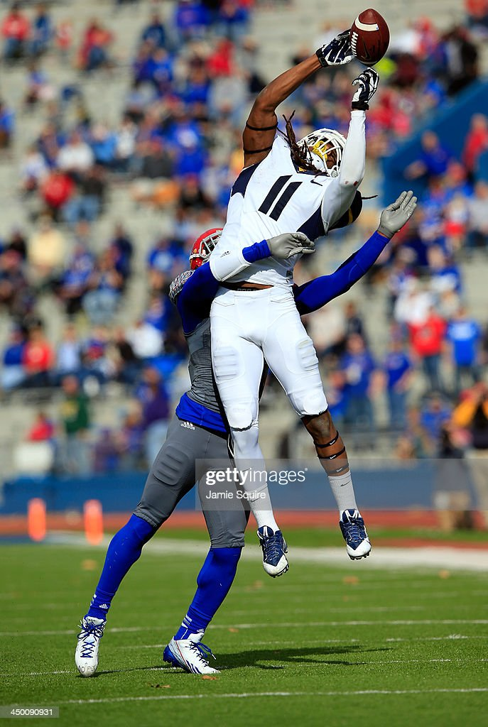 Cornerback Dexter McDonald #12 of the Kansas Jayhawks breaks up a pass intended for wide receiver Kevin White #11 of the West Virginia Mountaineers during the game at Memorial Stadium on November 16, 2013 in Lawrence, Kansas.