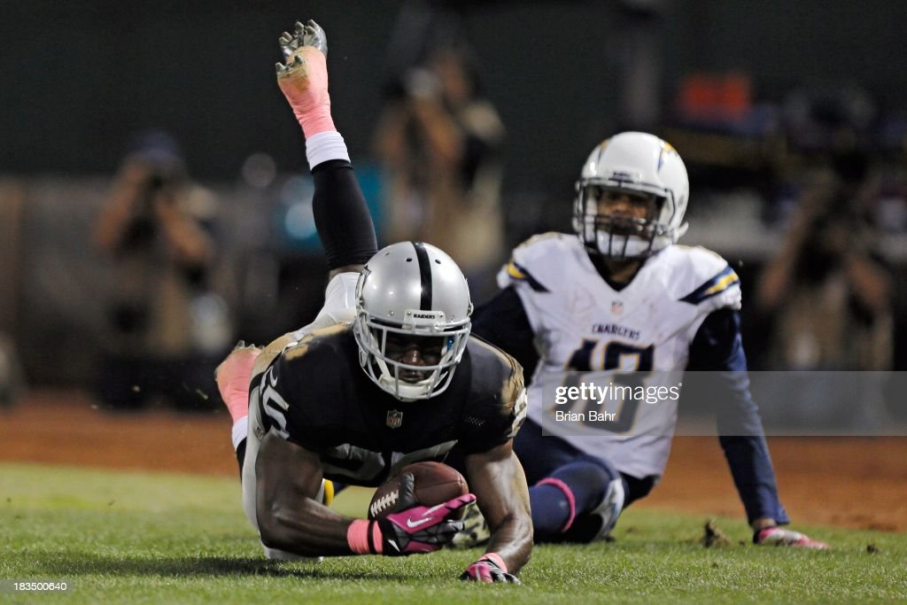 Cornerback DJ Hayden of the Oakland Raiders intercepts a pass in the endzone intended for wide receiver Keenan Allen of the San Diego Charges with...