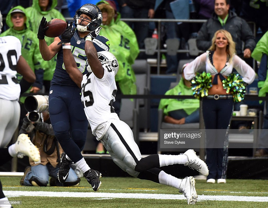 Cornerback DJ Hayden of the Oakland Raiders is called for interference as he goes up for the ball with wide receiver Jermaine Kearse of the Seattle...