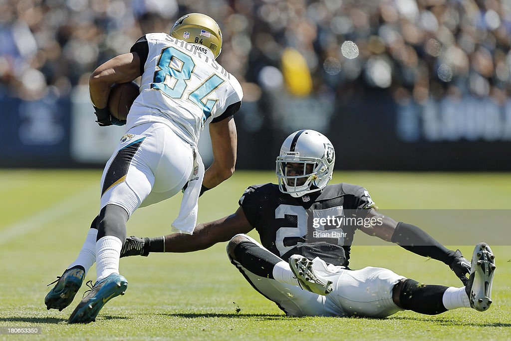 Cornerback DJ Hayden of the Oakland Raiders manages to tackle wide receiver Cecil Shorts III of the Jacksonville Jaguars while seated in the second...