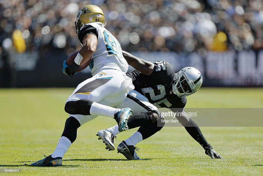Cornerback DJ Hayden of the Oakland Raiders tackles wide receiver Cecil Shorts III of the Jacksonville Jaguars as he falls down in the second quarter...