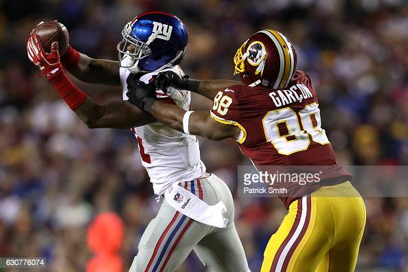 Cornerback Dominique RodgersCromartie of the New York Giants intercepts the ball in front of wide receiver Pierre Garcon of the Washington Redskins...