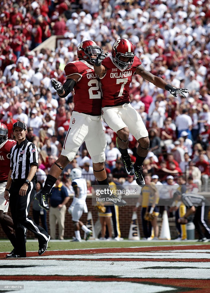 Cornerback Jordan Thomas and linebacker Jordan Evans of the Oklahoma Sooners celebrate a fumble recovery against the West Virginia Mountaineers...