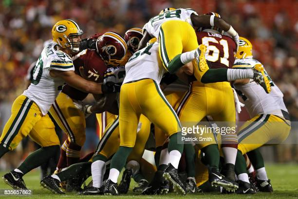 Cornerback Josh Hawkins of the Green Bay Packers piles on as teammates make a tackle against the Washington Redskins in the first half during a...