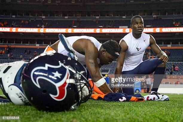 Cornerback Kayvon Webster of the Denver Broncos and defensive back Charles James of the Houston Texans exchange jerseys after a game at Sports...